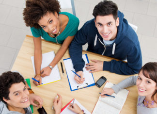 Group of young students studying together at library