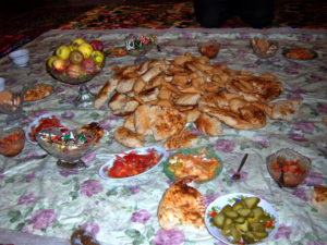 Kyrgyz village home, food spread on floor.