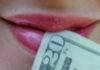 woman's mouth with $20 bill