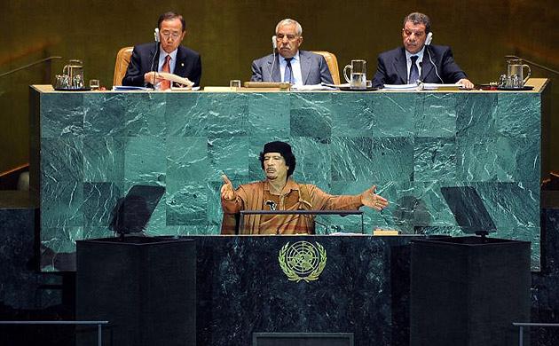 Muammar Gaddafi with his hands up. 3 UN people behind him